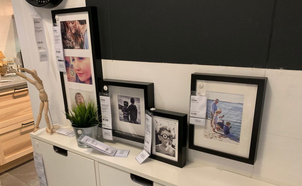 various sizes of black picture frames sitting on white console table