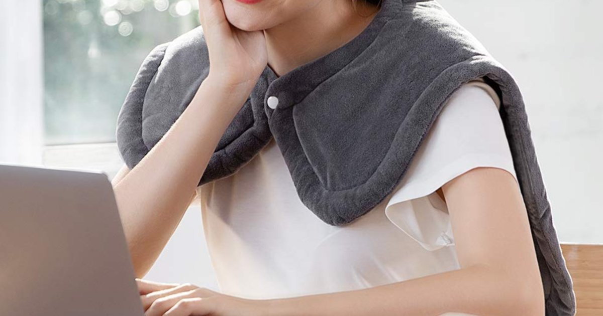 woman using laptop with heating pad wrapped around her