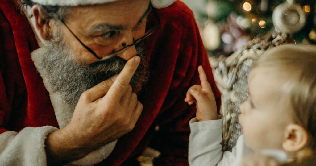 Santa Claus pointing to his nose while a baby watches