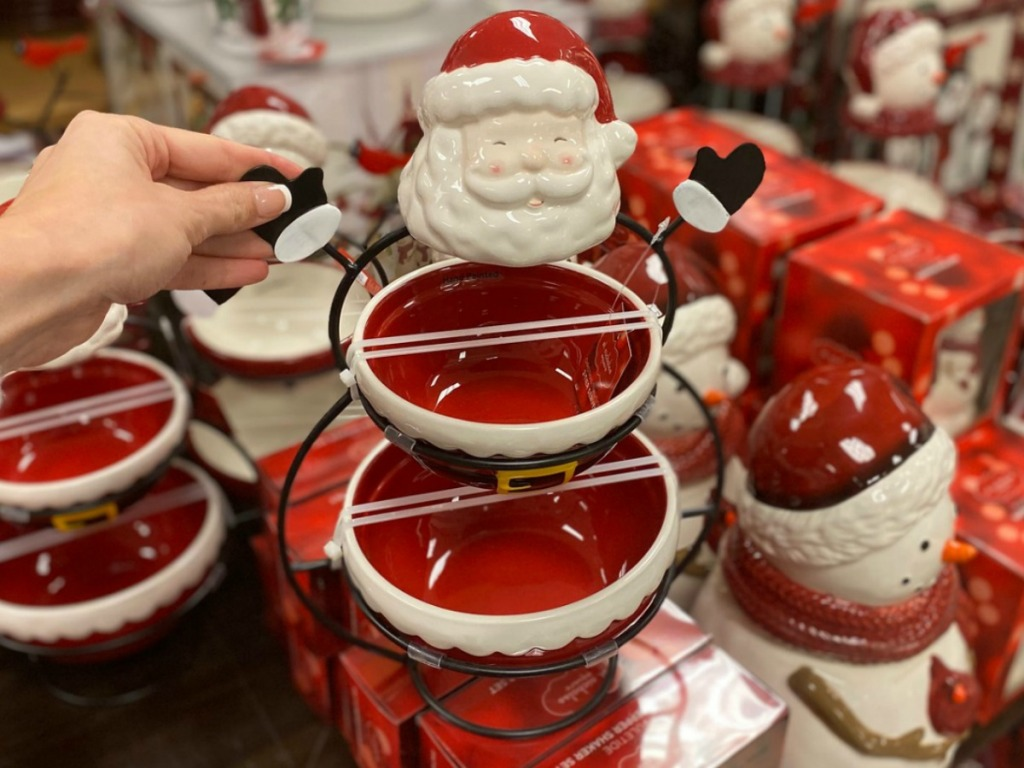 Hand holding a Santa Claus-themed two-tier serving tray