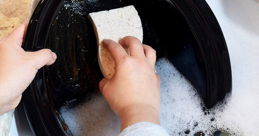 person washing dishes with a sponge