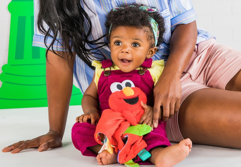 baby girl playing with elmo toy