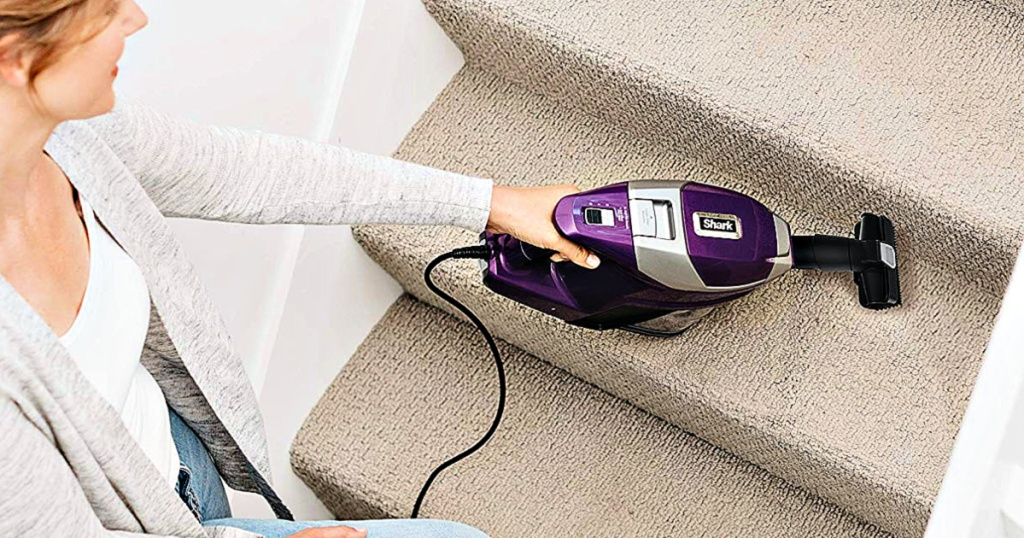 Shark Rocket Corded Ultra-Light Vacuum with Zero-M Anti-Hair Wrap Technology being used by woman on stairs