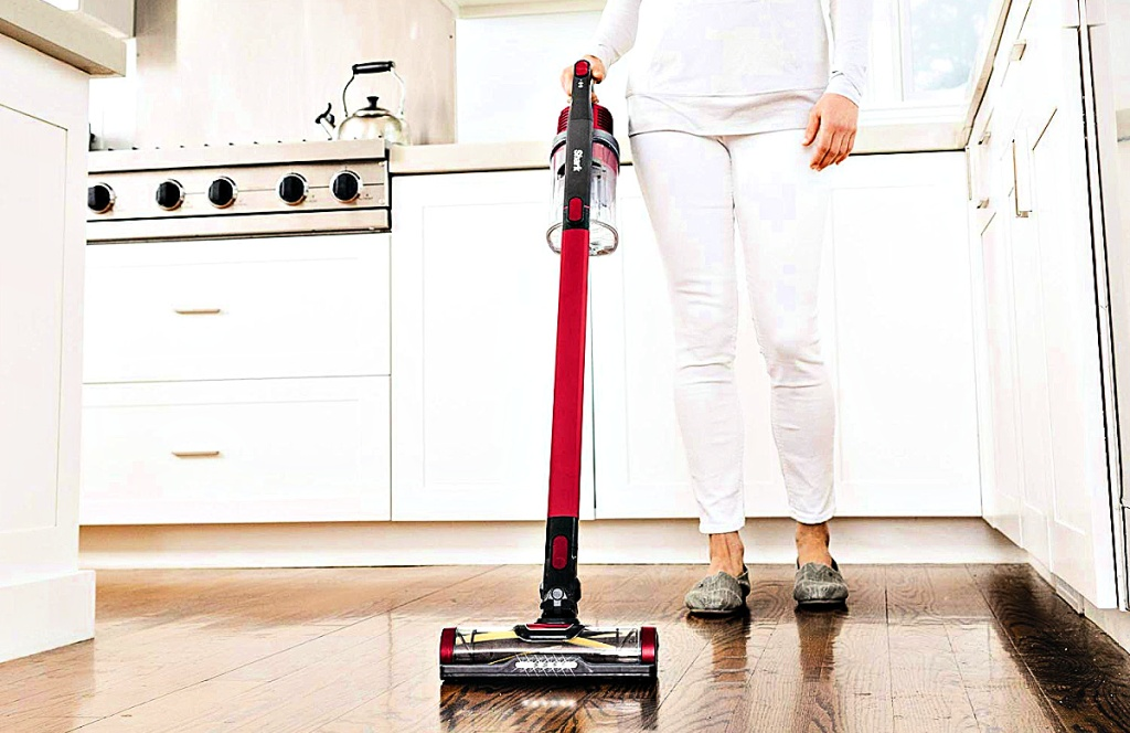 Shark Rocket Pet Pro Lightweight Cordless Stick Hand Vacuum with Self-Cleaning Brushrollbeing used by woman in kitchen