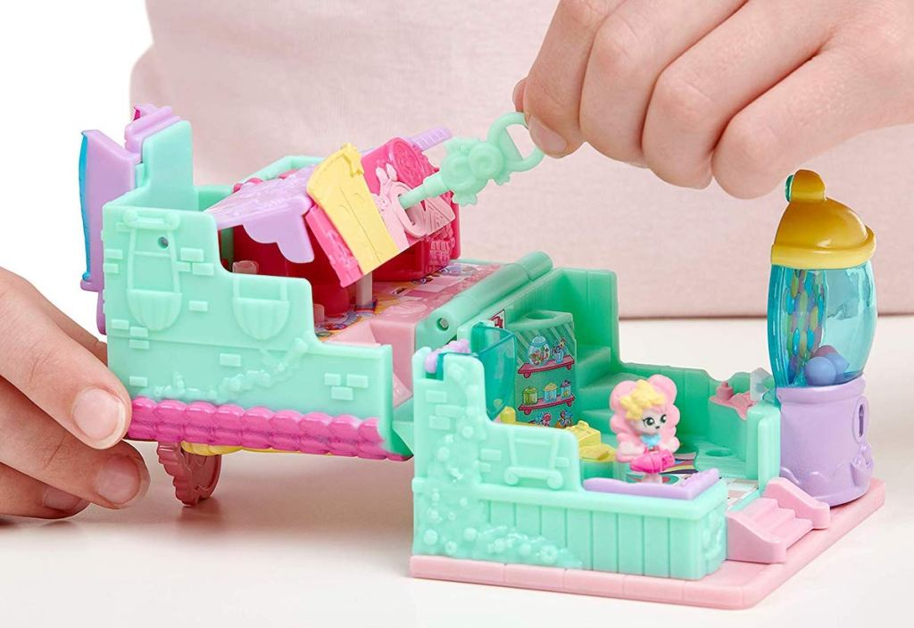 child playing with Shopkins Lil Secrets Mini Playset - Sweet Retreat Candy Shop with key