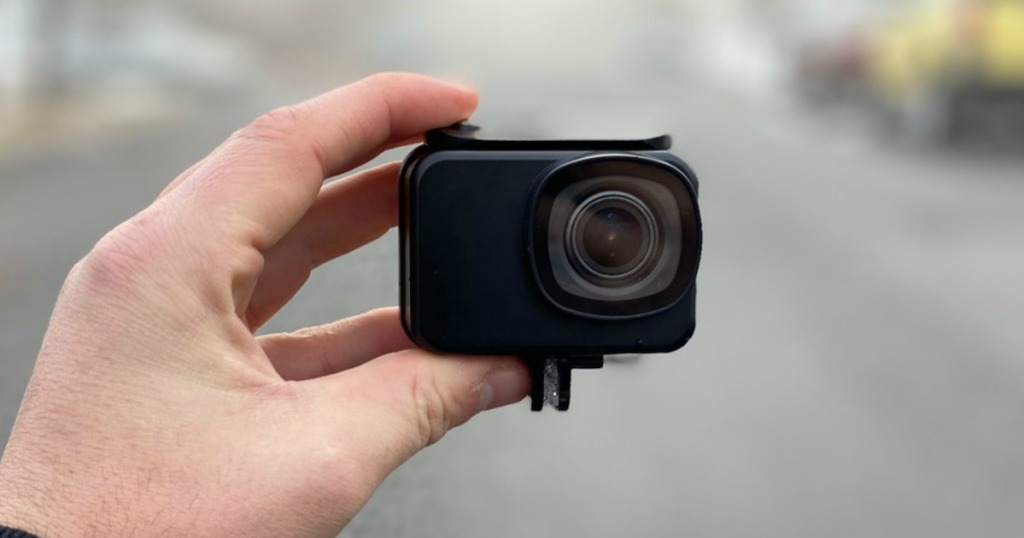 man holding a small action camera
