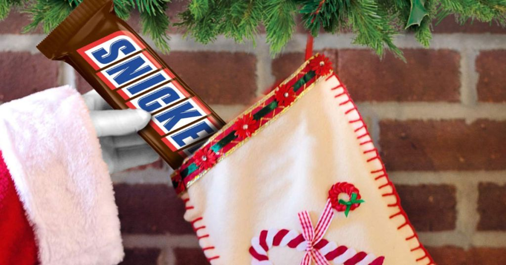 Santa hand putting giant snickers into stocking hanging on brick mantle with garland