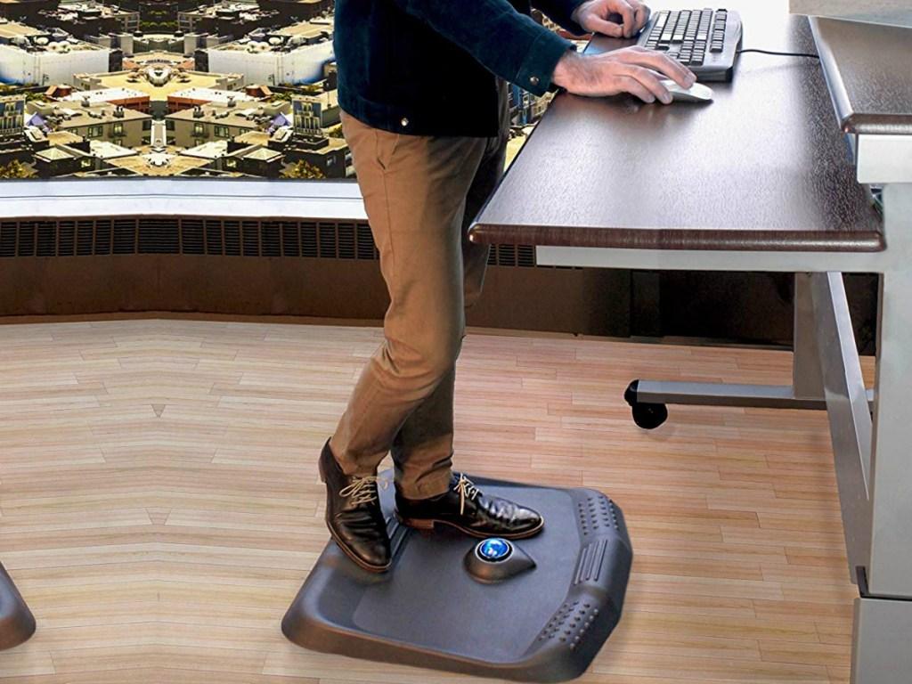 Man standing on mat at desk