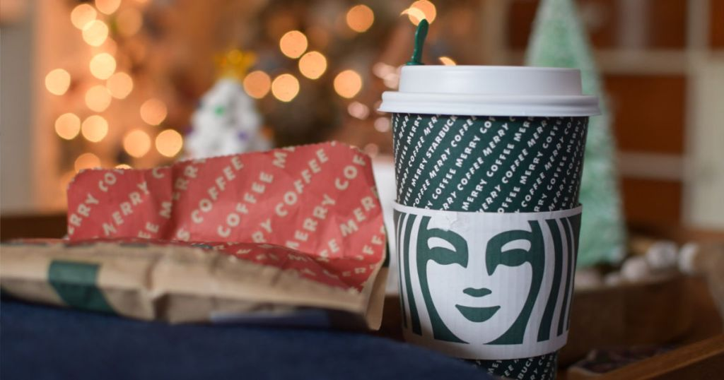 Starbucks holiday cup with lights in the background