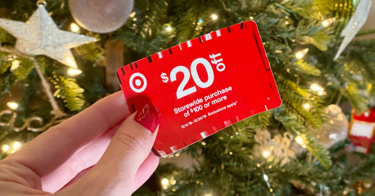 Woman holding Target coupon in front of Christmas Tree