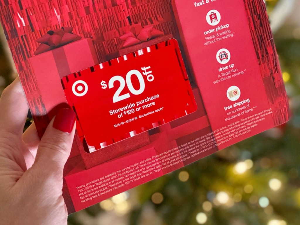 Woman holding Target Mailer Coupon in front of Christmas Tree