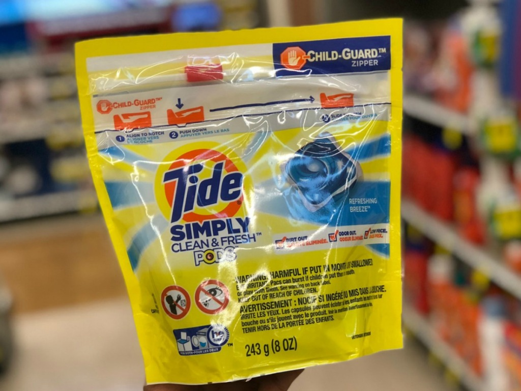 Tide pods package in hand in store near shelf