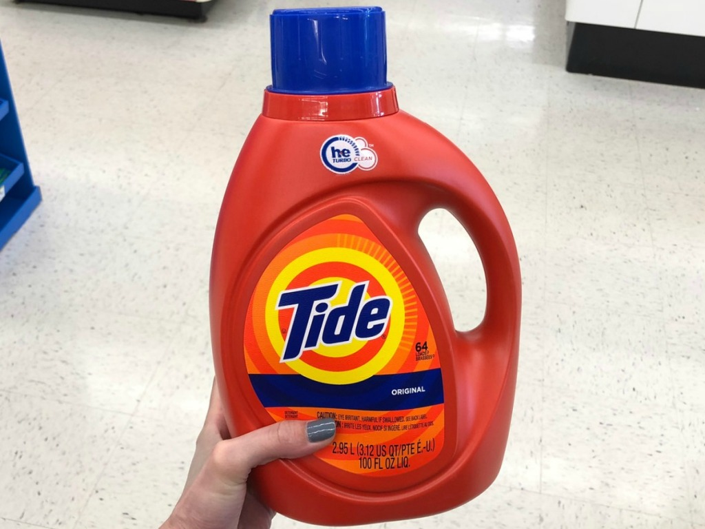 Bottle of Tide laundry detergent in hand