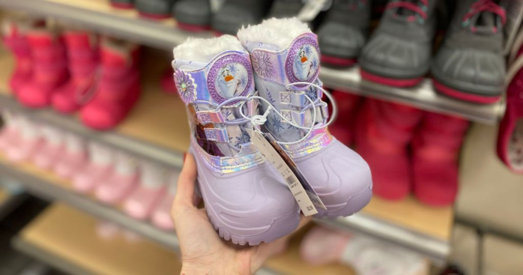 woman hand holding toddler girls frozen winter boots in store at target