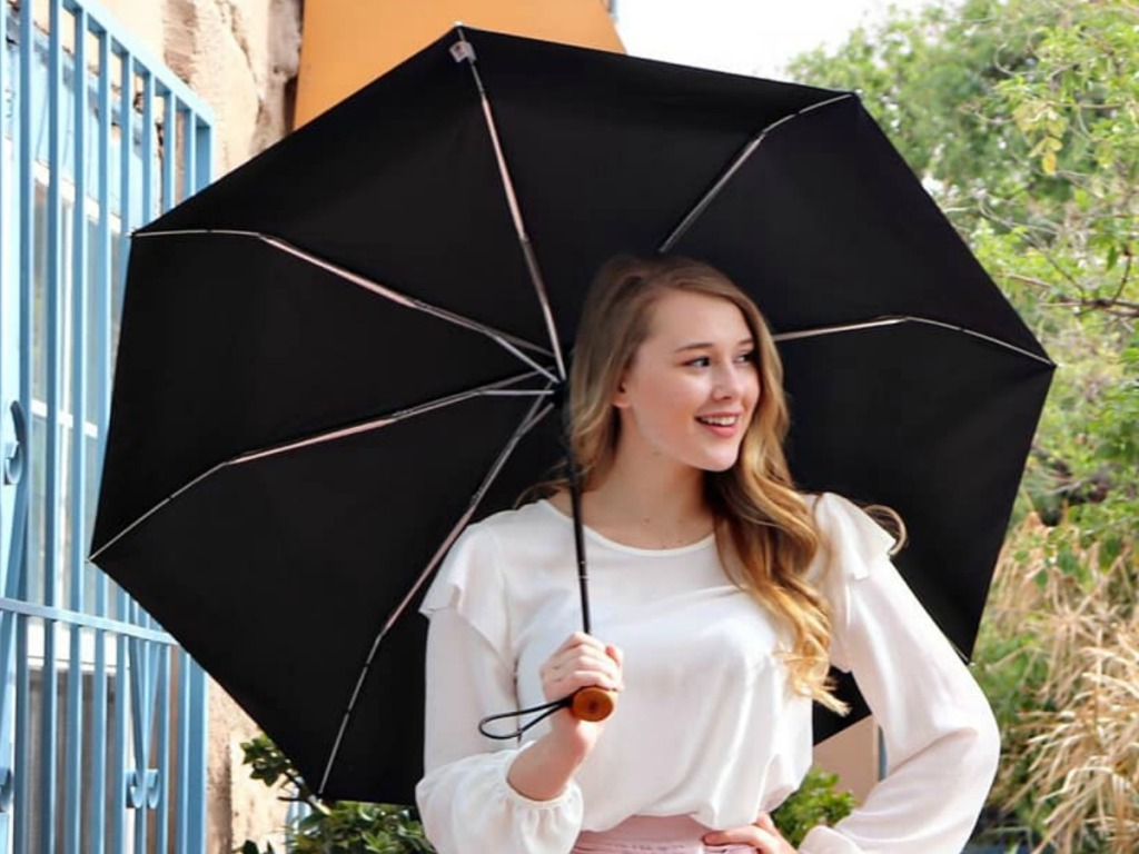 Woman holding a black totes umbrella