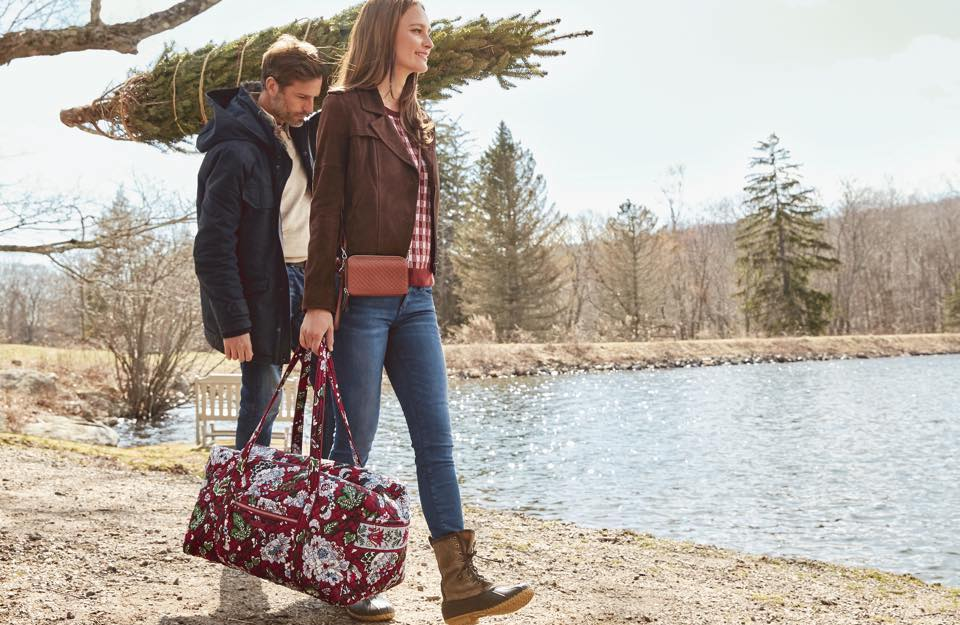woman carrying a Vera Bradley Duffel bag and man carrying a tree