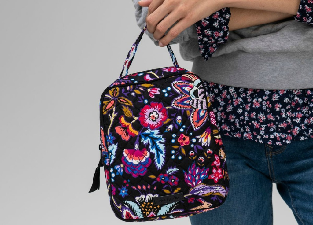 woman holding a floral multicolored lunchbag