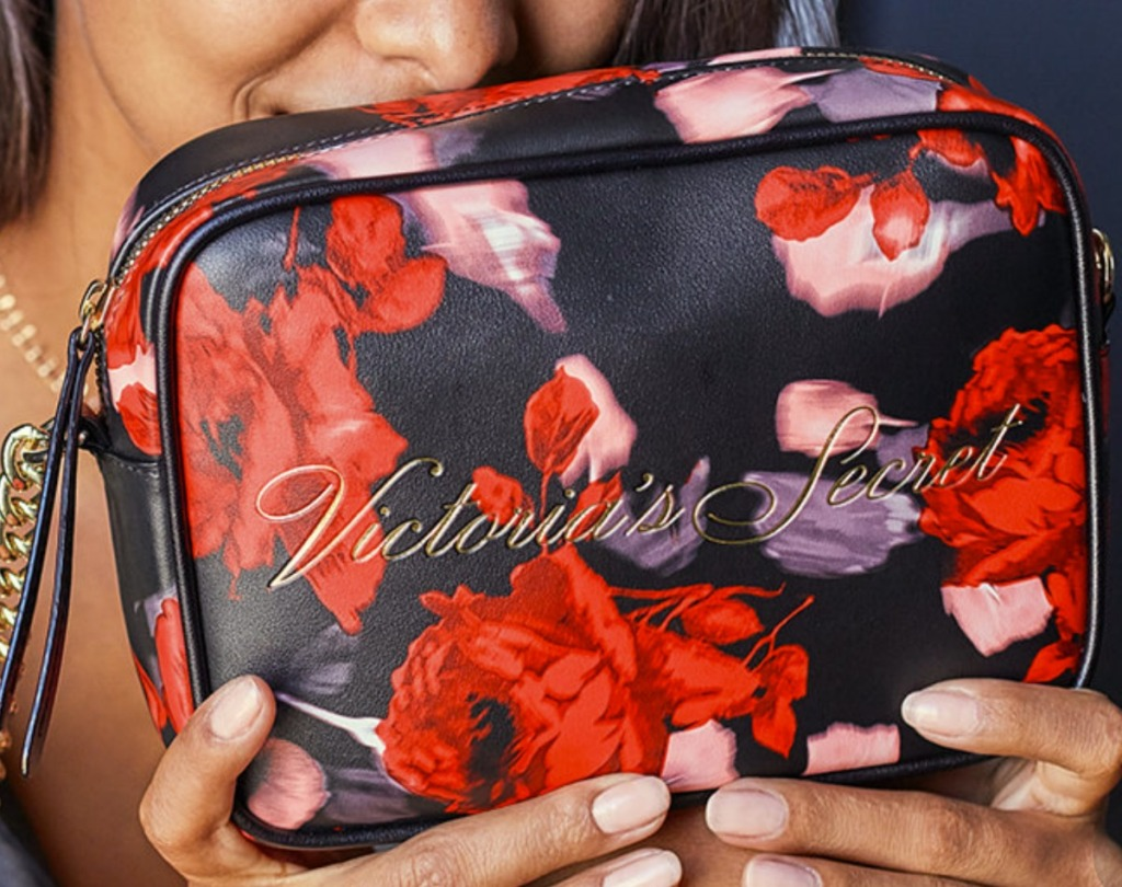 Woman holding a floral Victoria's Secret Crossbody Bag