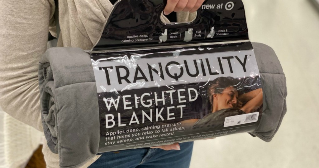 Woman holding a weighted blanket in the package