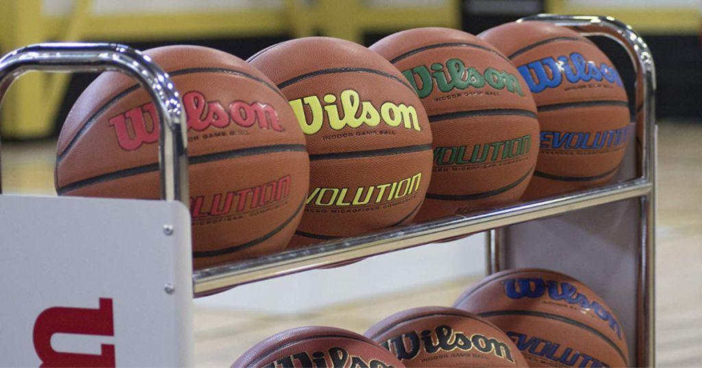 multiple wilson evolution basketballs on a rack inside gym