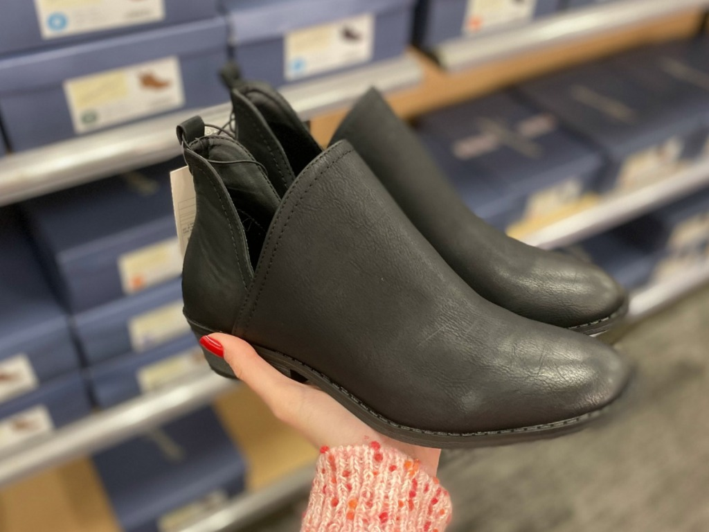 Women's Boots in black in hand near in-store display