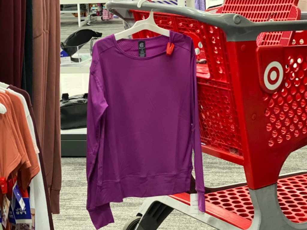 Women's purple active shirt hanging on a red Target shopping cart