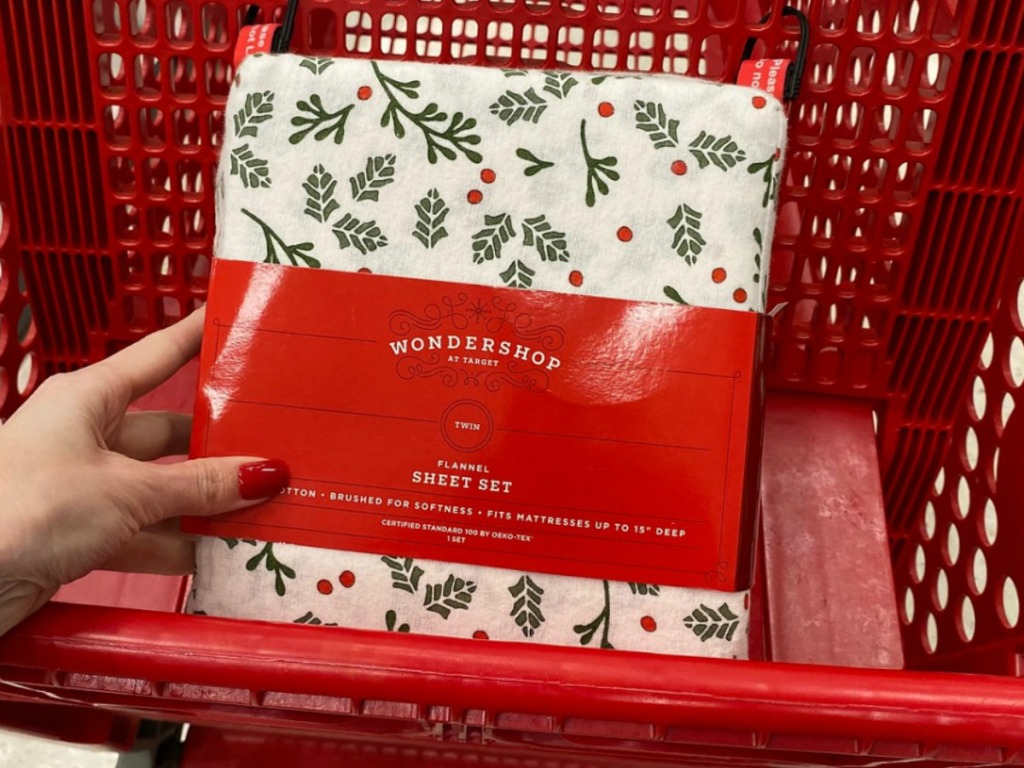 A holiday holly-print sheet set in package in red Target shopping cart