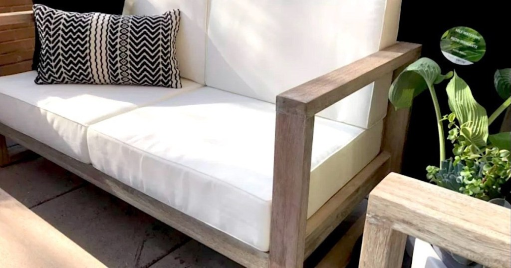 modern wood patio couch with white cushions and throw pillow sitting outside