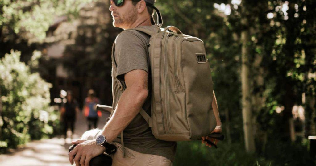 man wearing tan YETI Tocayo 26 Backpack in Black on bike