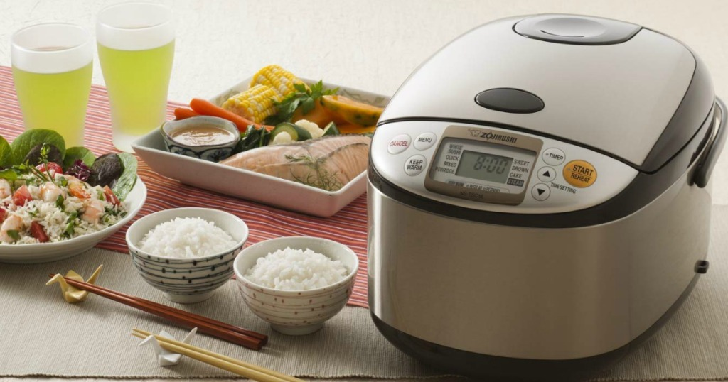 Zojirushi rice cooker next to bowls of rice, drinks and two meals