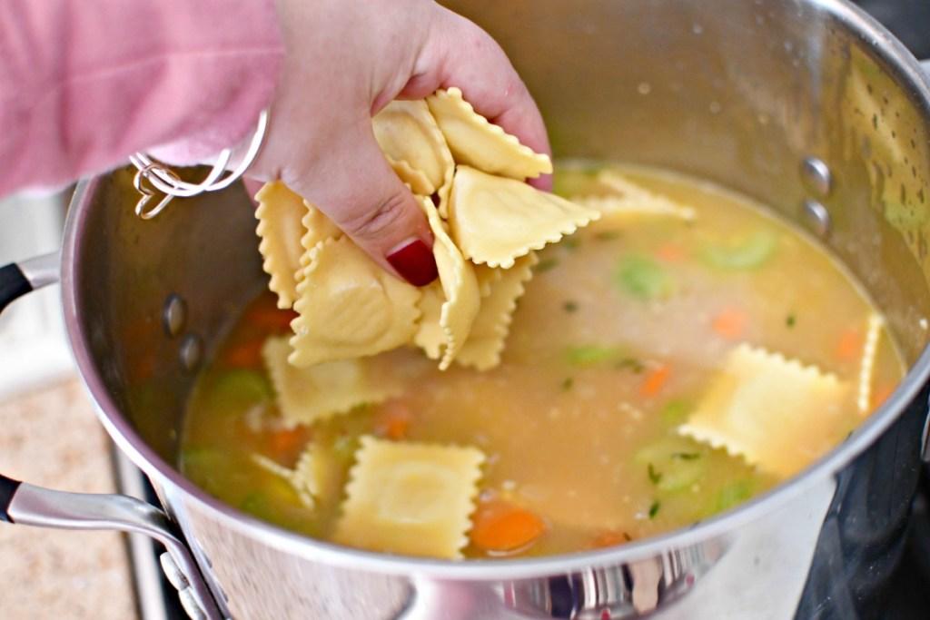 adding raviolis to creamy ravioli soup