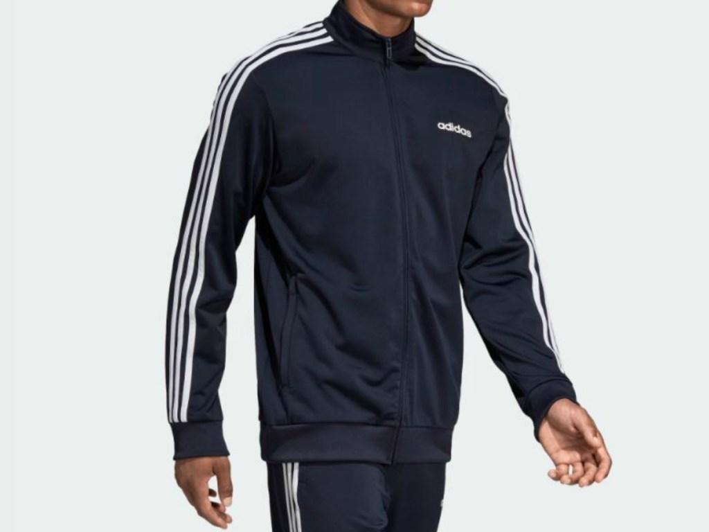 man walking wearing navy blue tracksuit