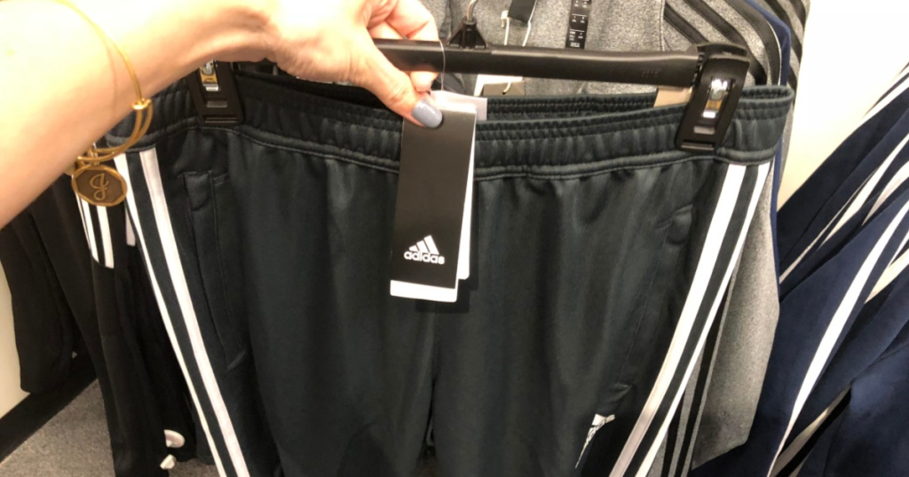 hand holding up pair of adidas shorts