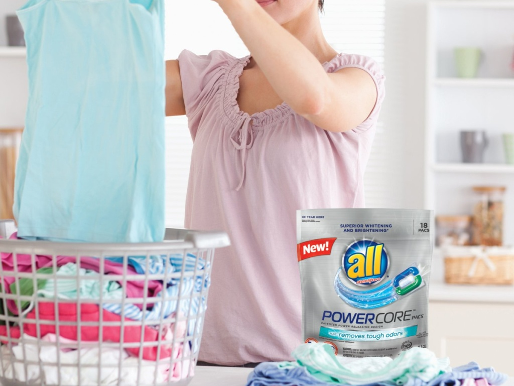 woman folding laundry with all powercore laundry detergent on table