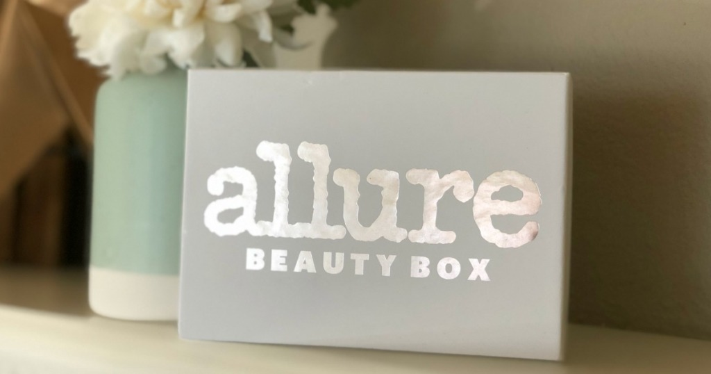 "box next to vase with words ""allure"" on it"