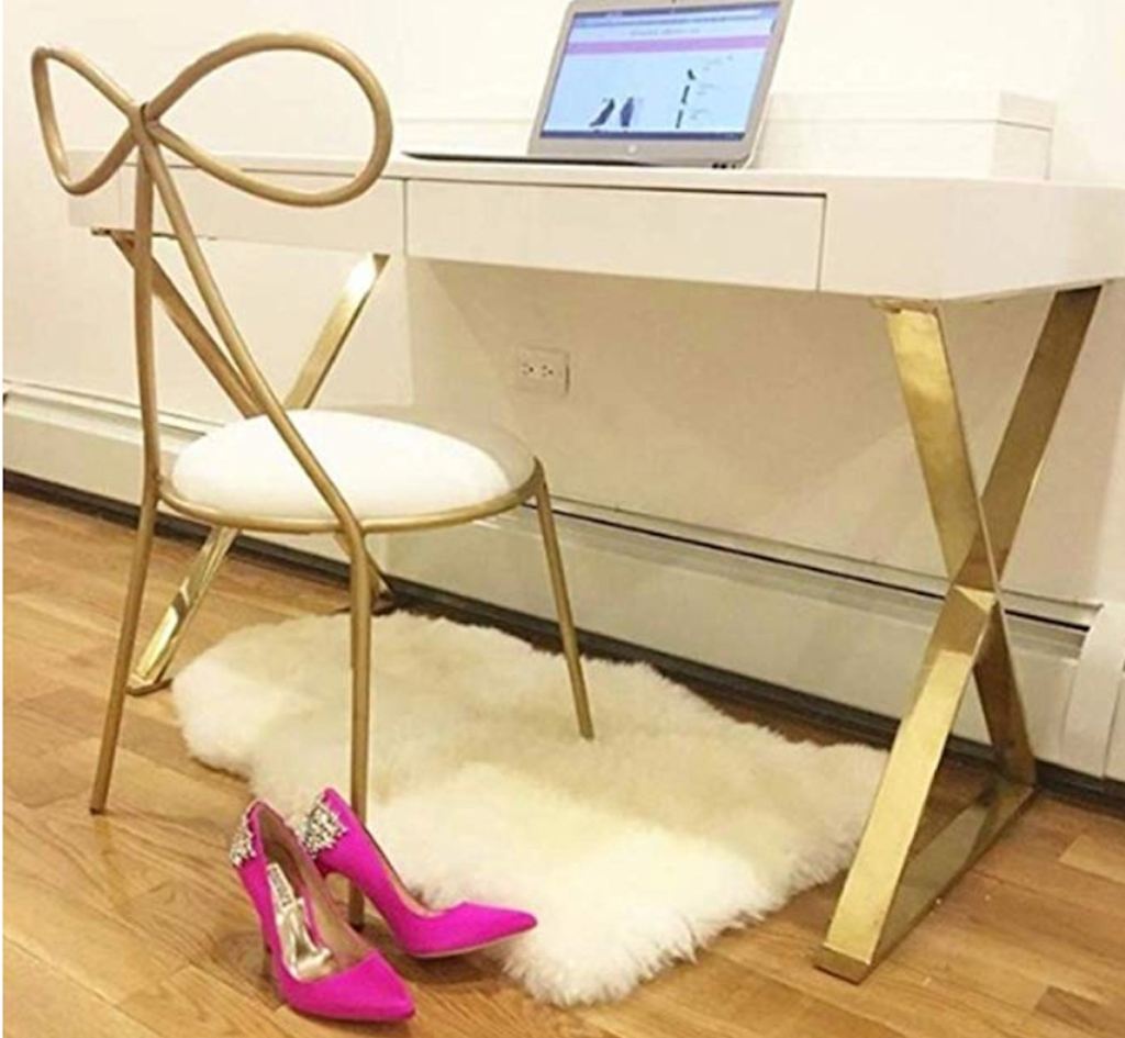 gold bow shaped chair and office desk with computer and hot pink high heels