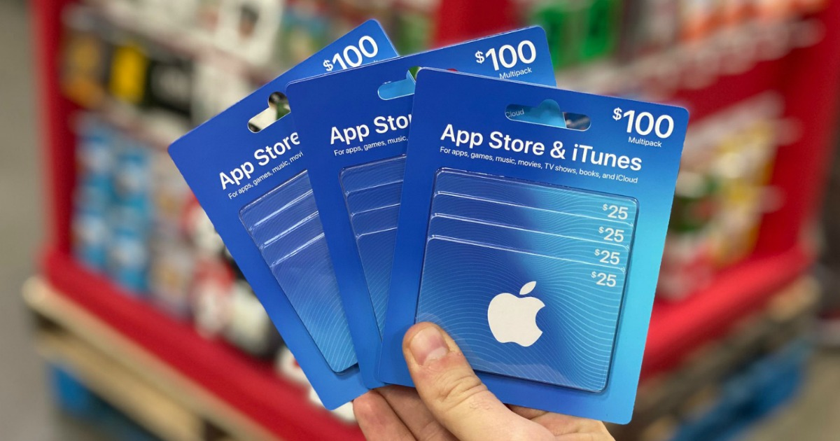 hand holding 3 iTunes gift cards in store