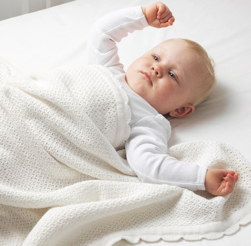 Baby laying on bed with white blanket on top