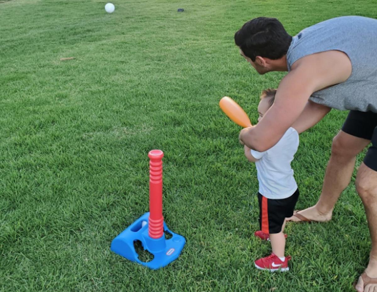 man and toddler hitting baseball bat on tball toy