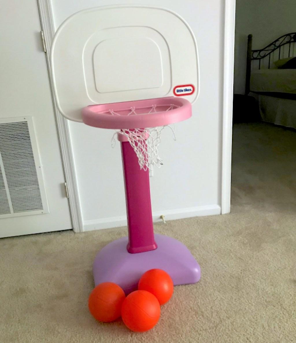 pink and purple kids basketball hoop with three orange balls on carpet