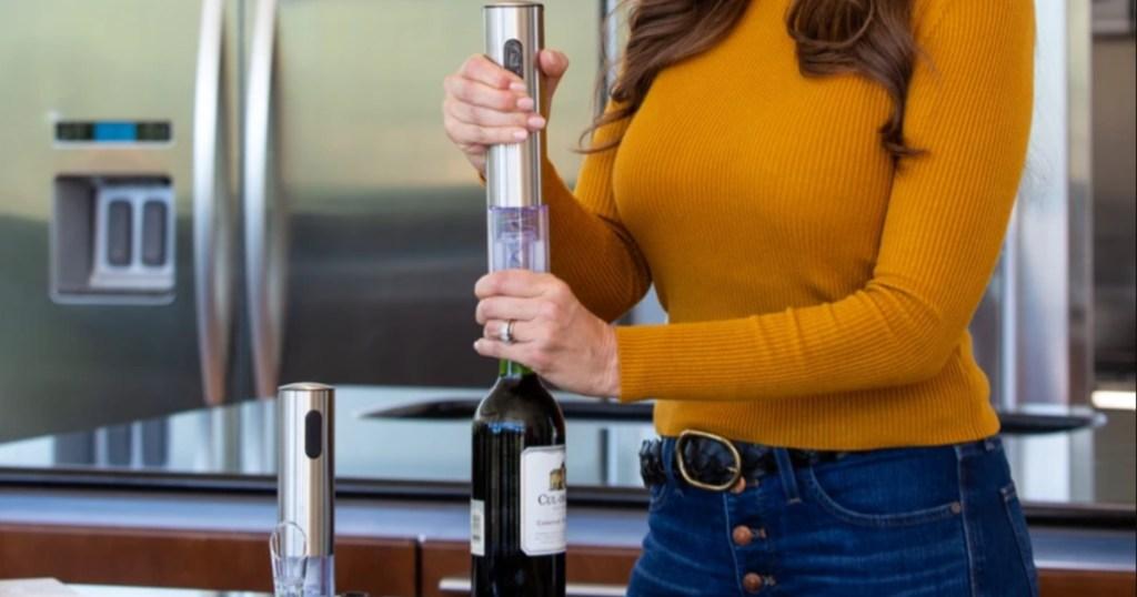 woman using wine opener on bottle of wine