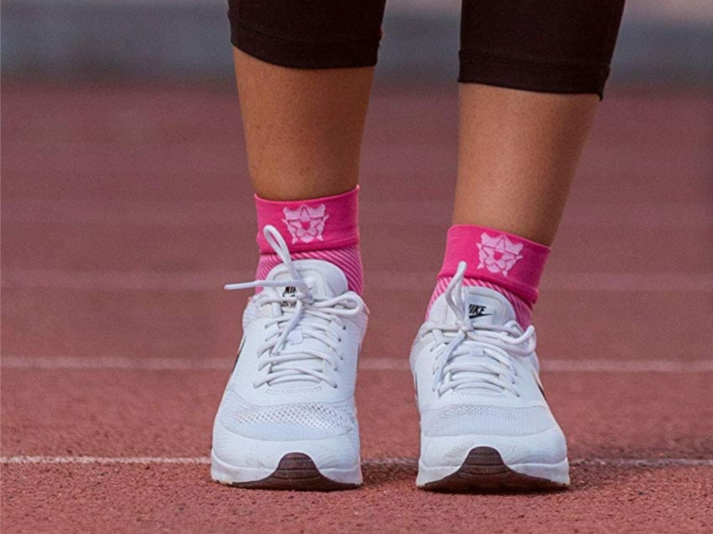 woman legs with pink compression socks on under white shoes