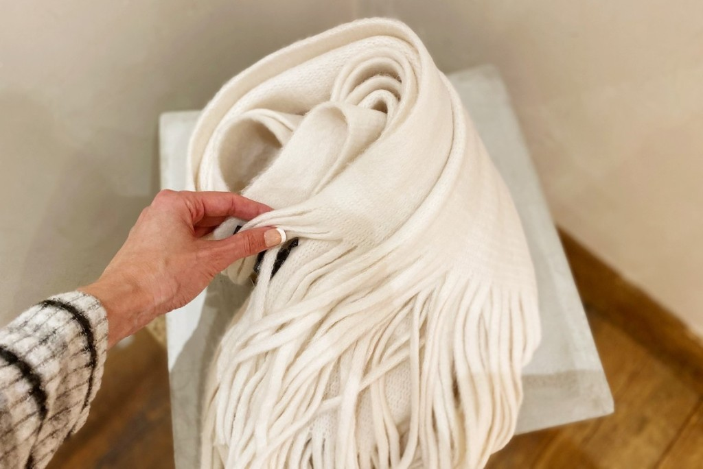 hand touching white fringed scarf