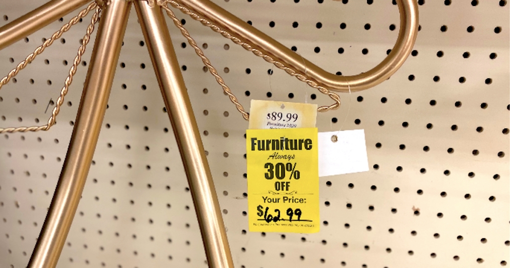 yellow furniture sale tag hanging from brass metal on store shelf