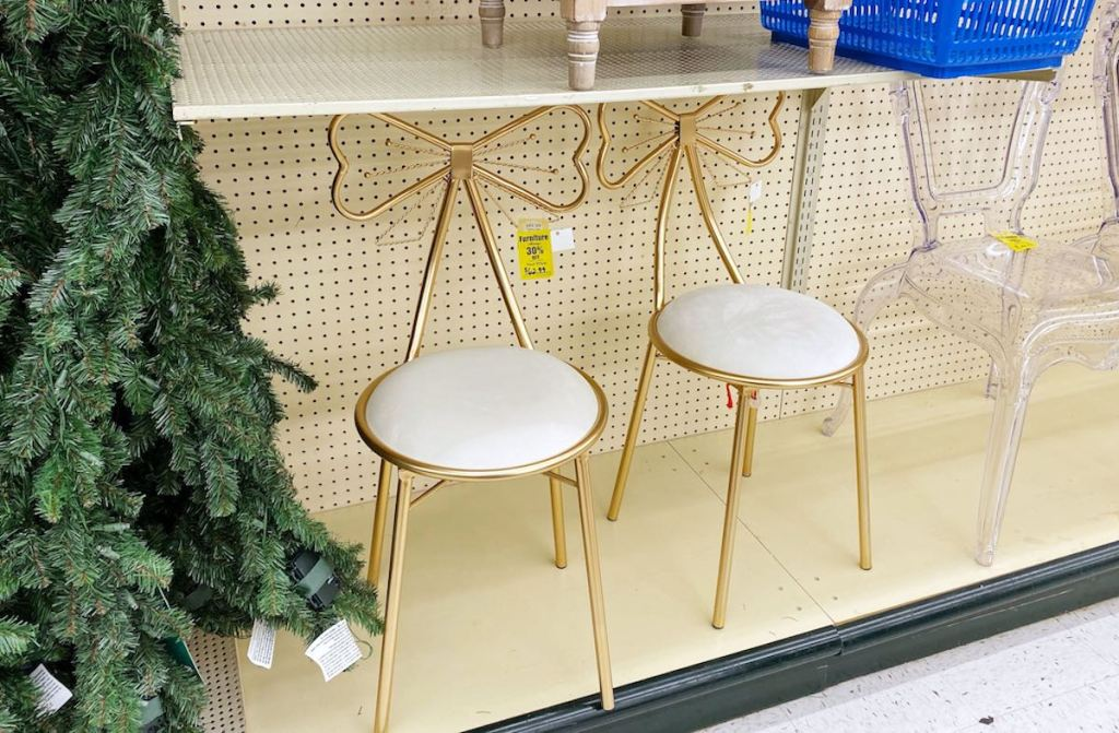 two gold bow chairs sitting on store shelf