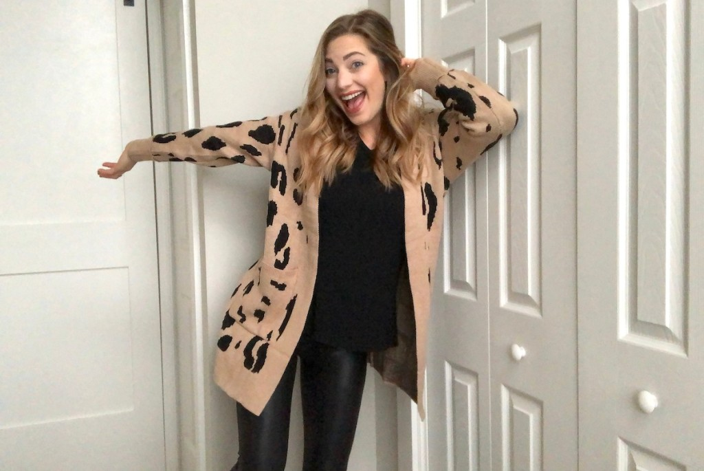 woman smiling and happy wearing beige and leopard cardigan with black shirt and leggings