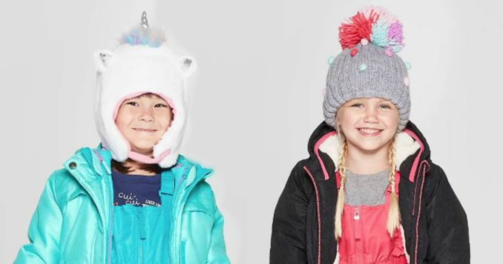 two little girls wearing snow hats and smiling