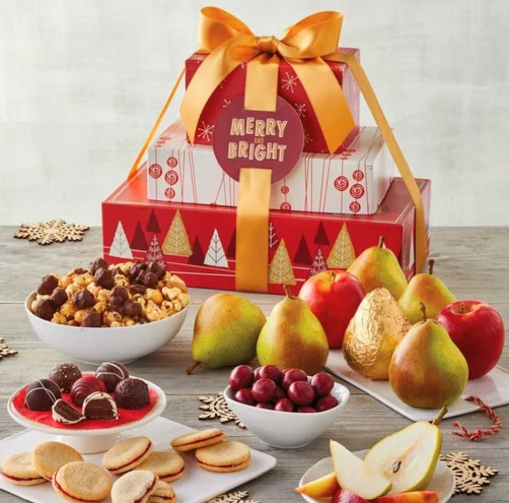tower of wrapped gifts with merry and bright tag and various types of food on table