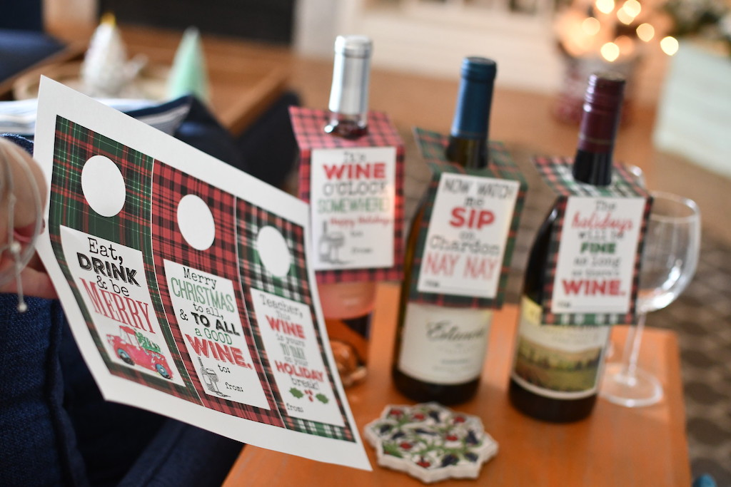 holding printable Christmas wine tags with wine bottles in the background