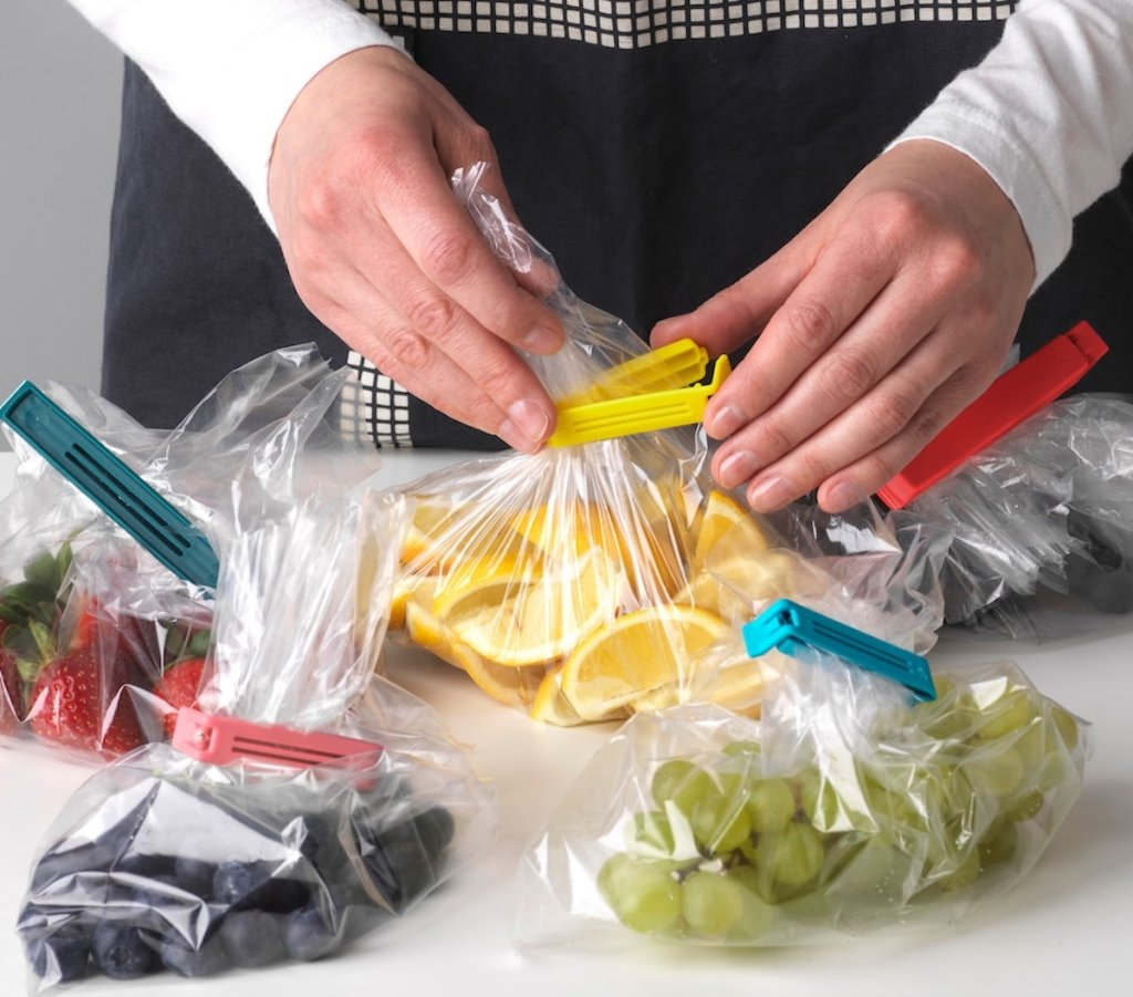 hands closing yellow clip on clear bag with food inside